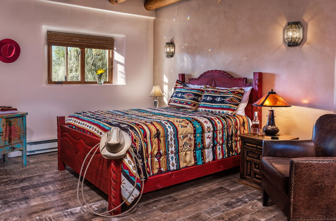 colorful bed behind fireplace and seating