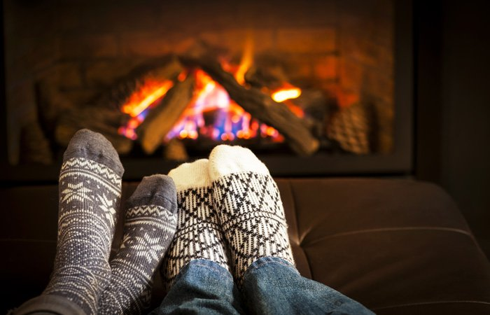 Two sets of feet in warm socks by a fireplace