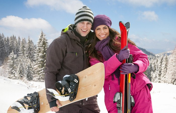 A couple with snowboard and skis
