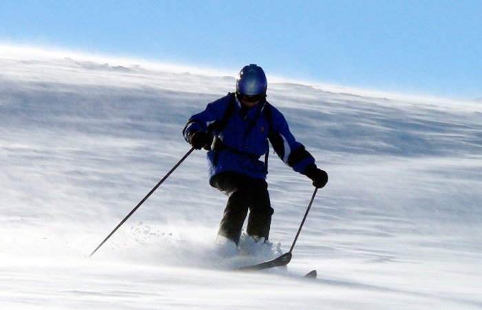 A person downhill skiing