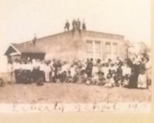 Sepia photo of a schoolhouse with children on the roof