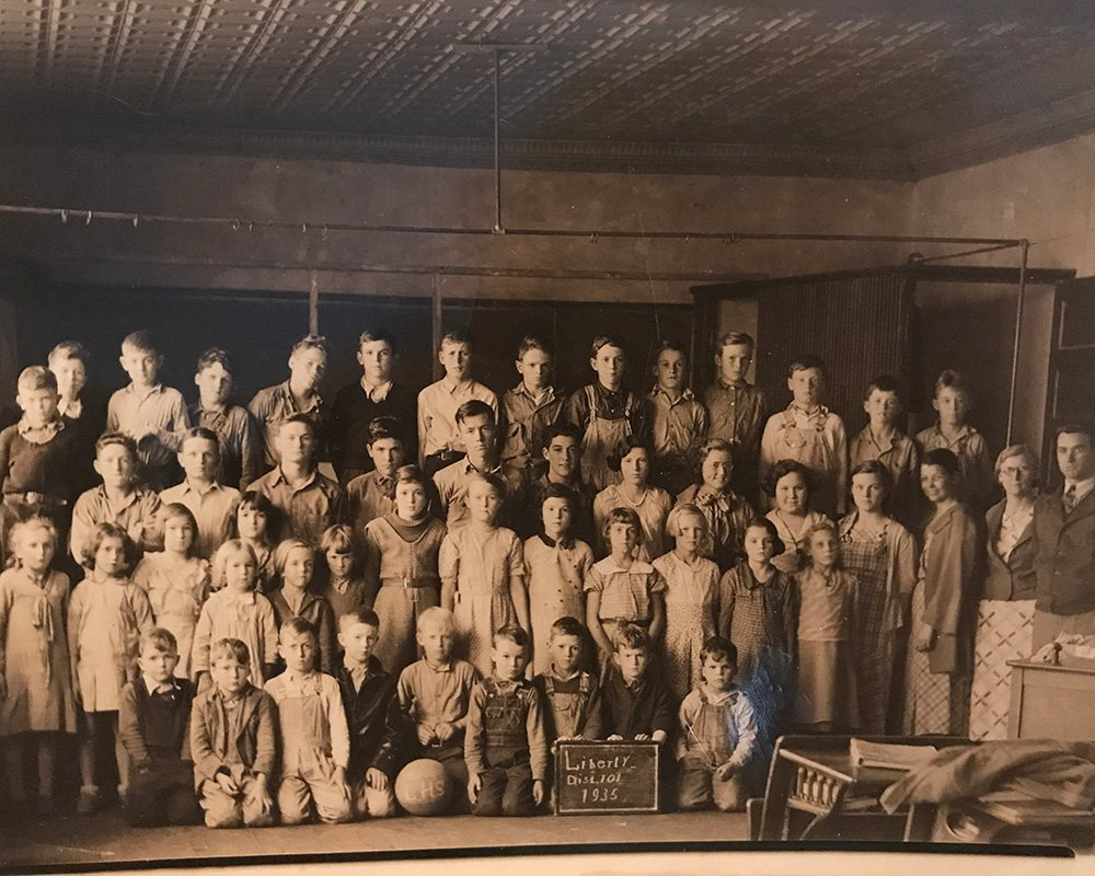 A sepia photo of schoolchildren in an old schoolhouse