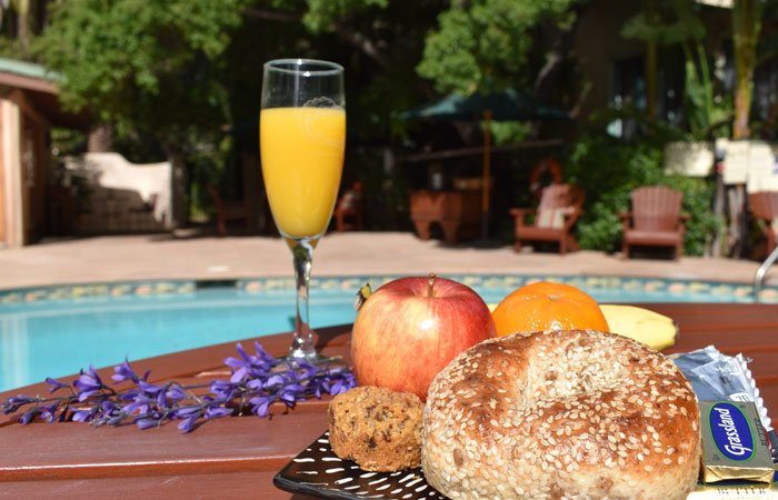 Glass of orange juice with bagle and other snacks by the pool