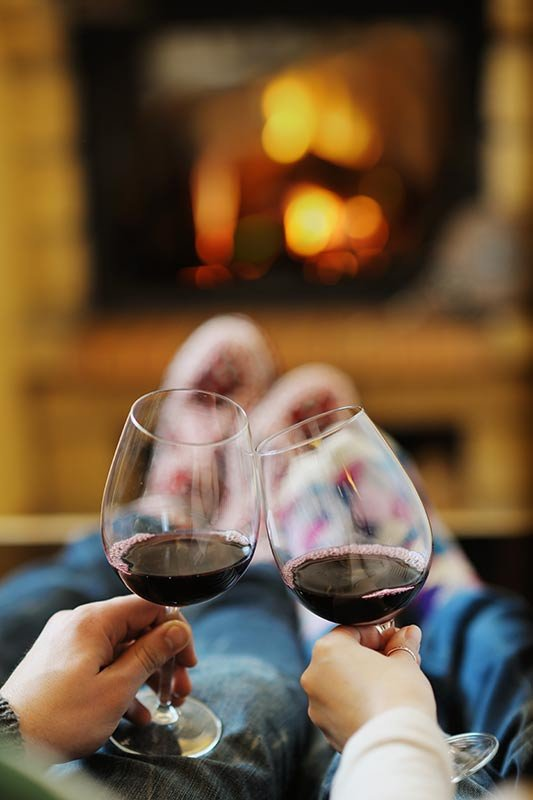 view of couple clinking wine glasses in front of fire