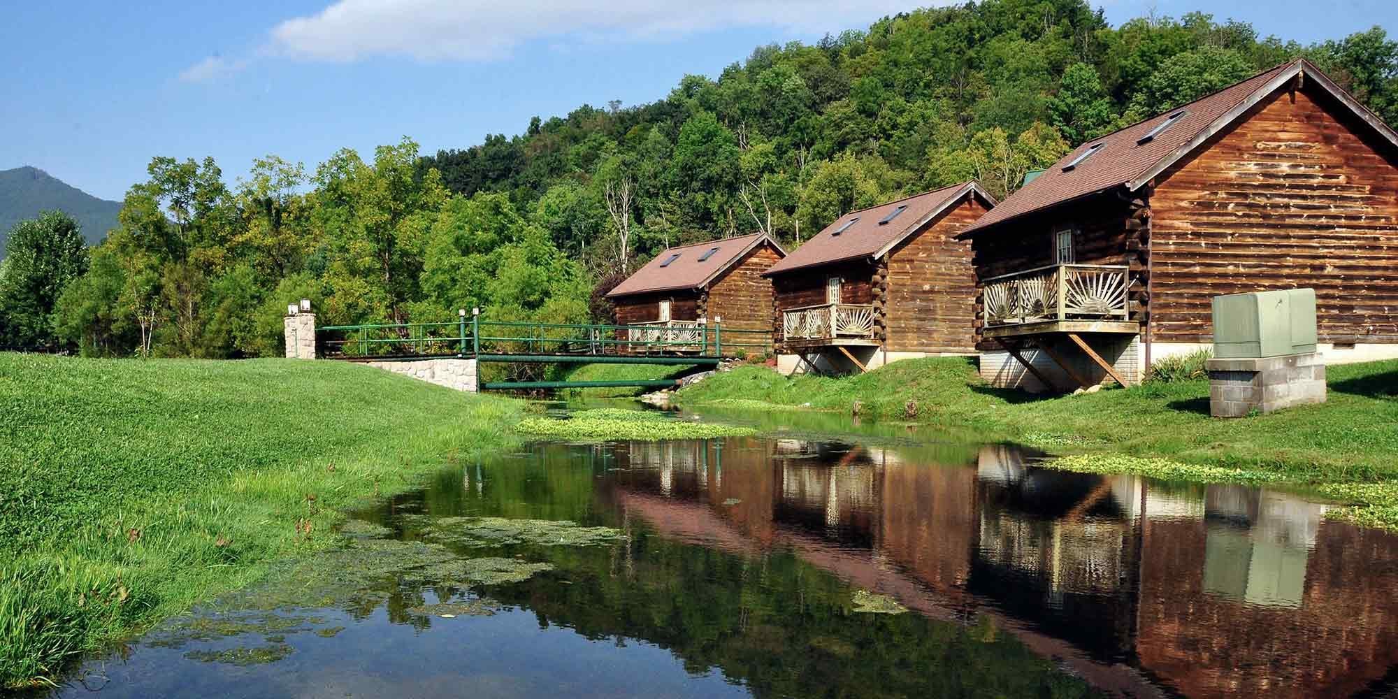 Log cabins beside small body of water