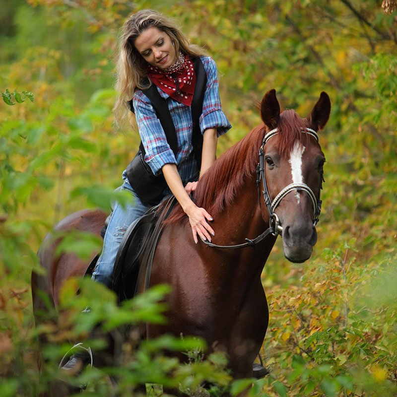 woman riding and petting horse