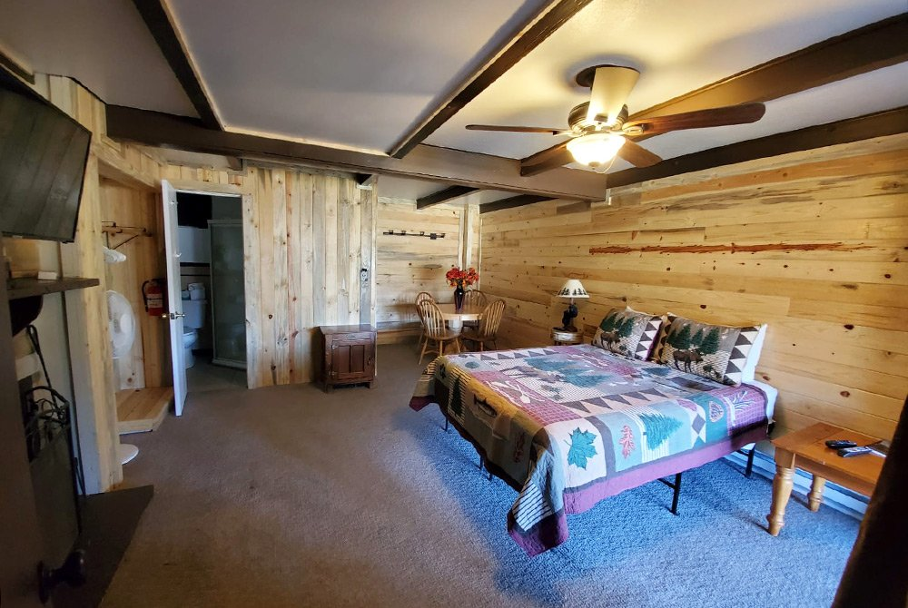 Bed under ceiling fan in large room