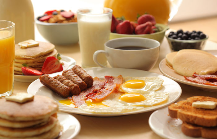 Bacon and eggs with coffee, sausage, toast, fruit