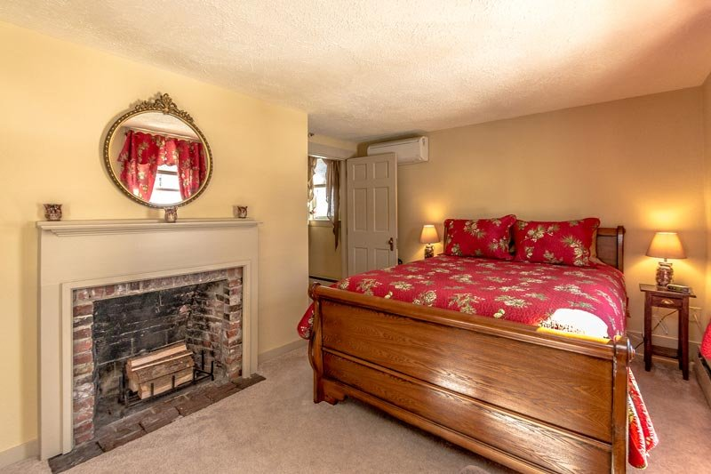 A fireplace and a bed with red covers