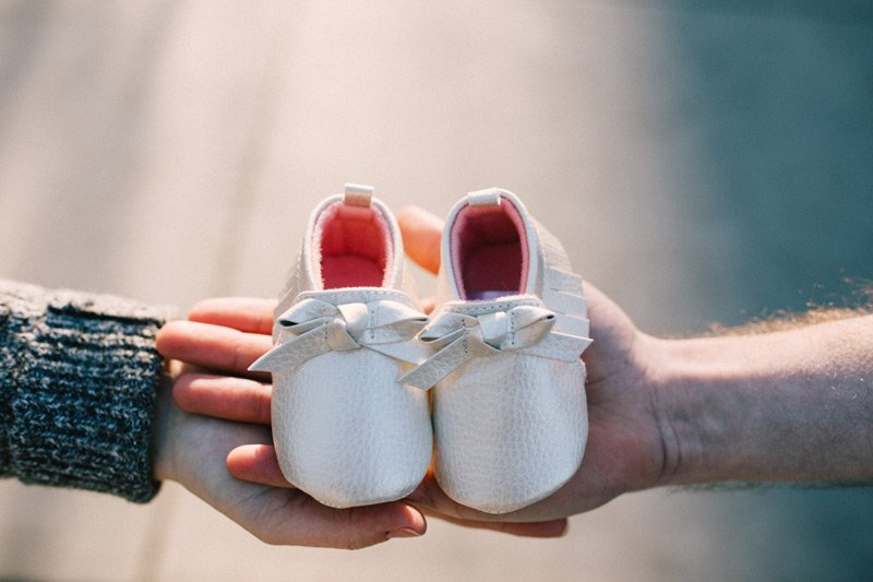 hands holding baby shoes