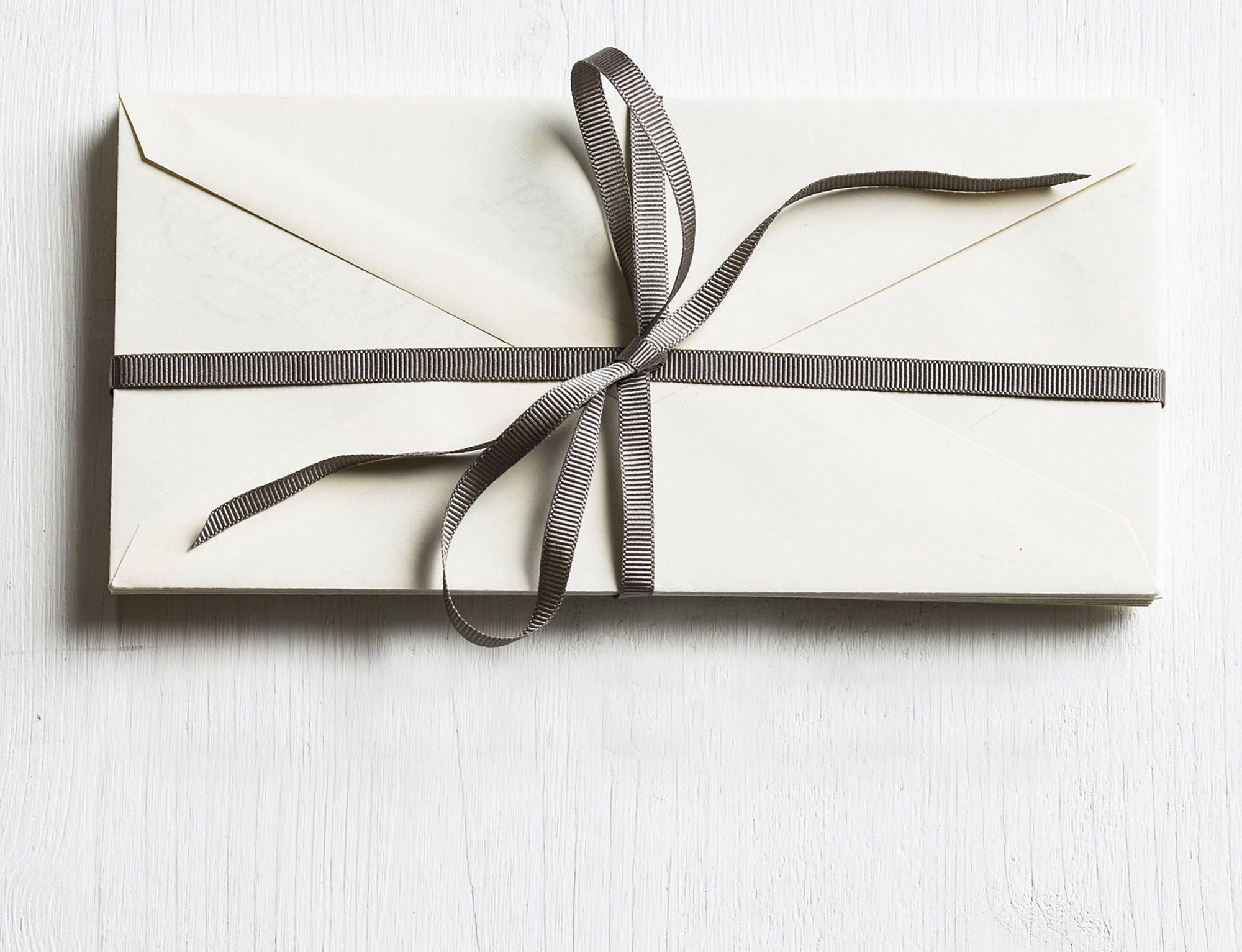 white envelop wrapped with grey ribbon