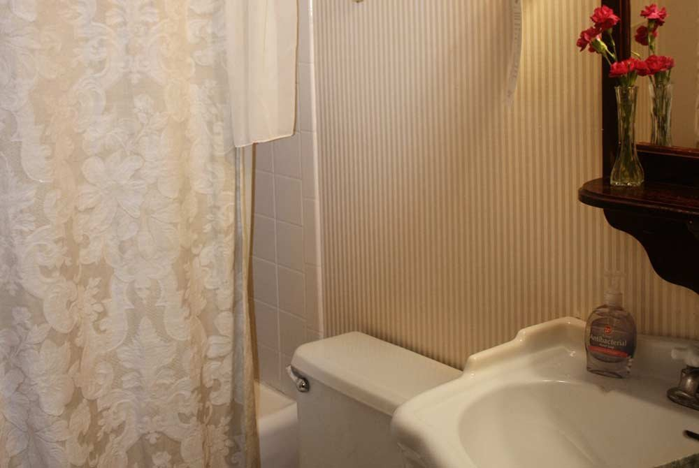 bathroom with sink, toilet, tub and striped wallpaper