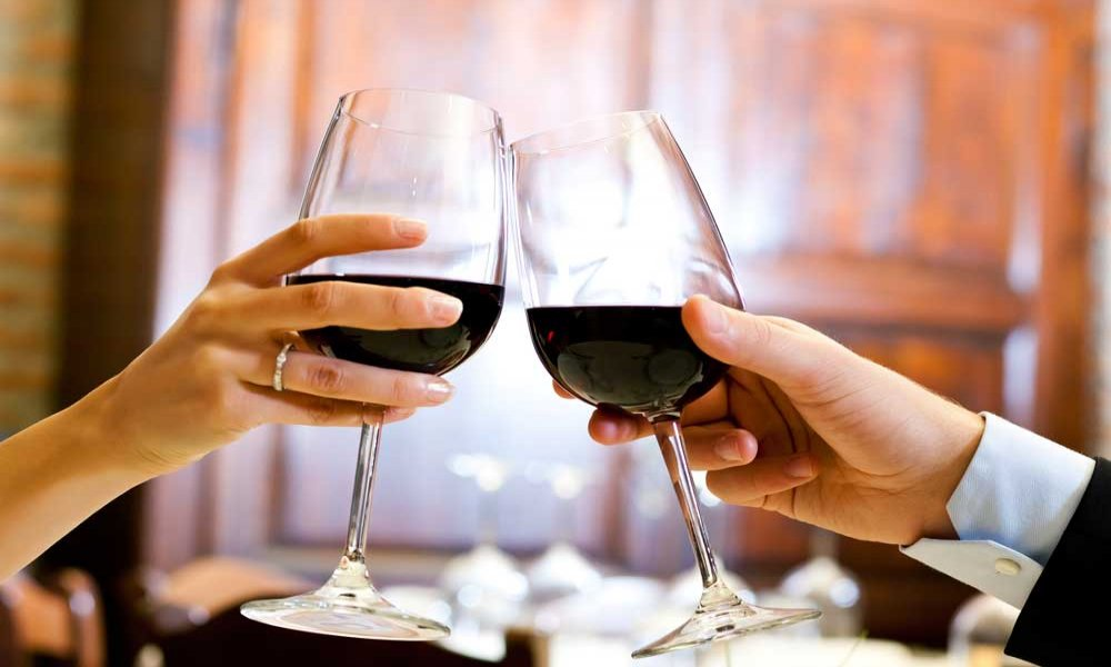 Two people toasting with wine glasses