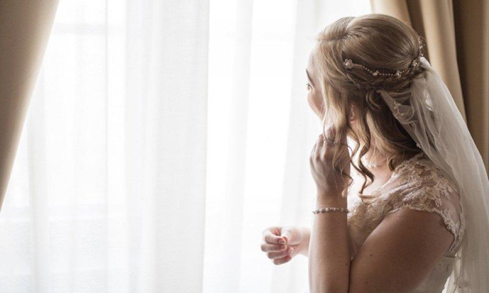 woman in wedding dress putting in earring