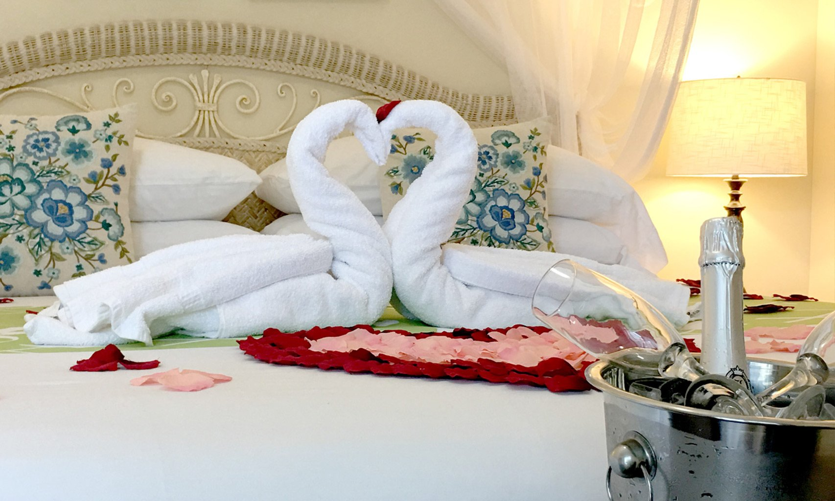 Towels folded into a pair of swans on a bed