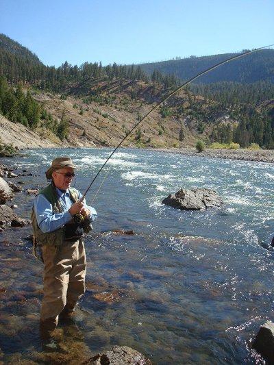 happy man fly fishing in a stream