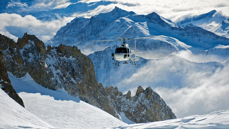 Helicopter flying among snowy mountains