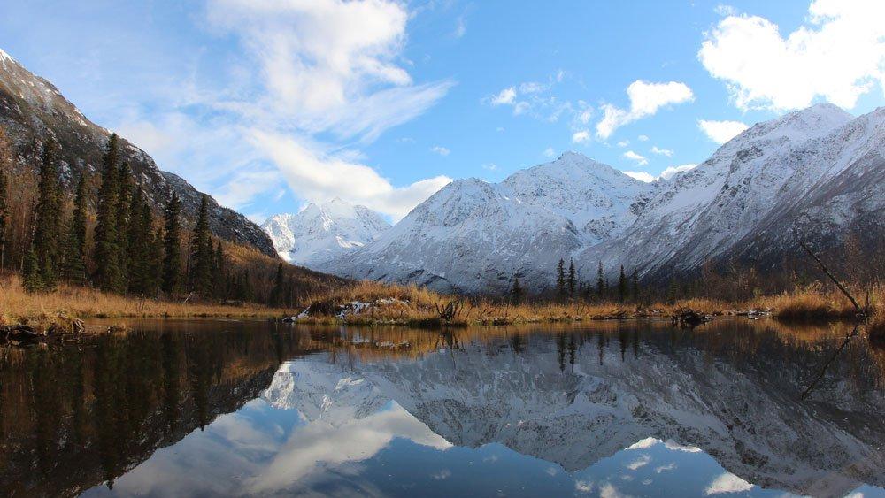 Glassy lake beneath snowy mountains