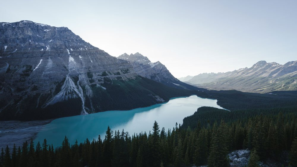 tall, bare mountains standing over blue waters