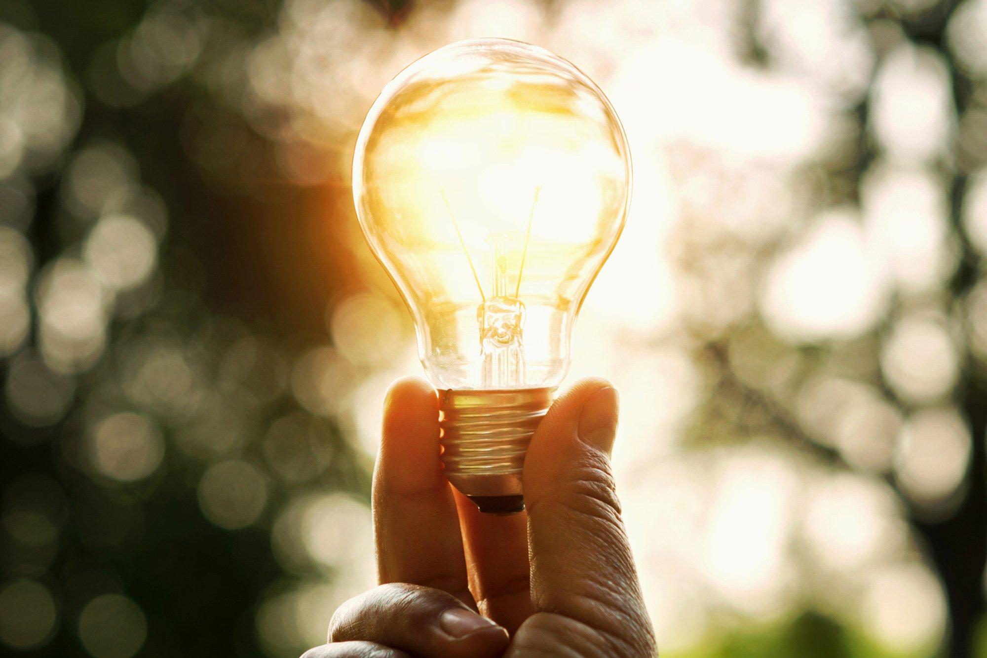 person holding lit light bulb
