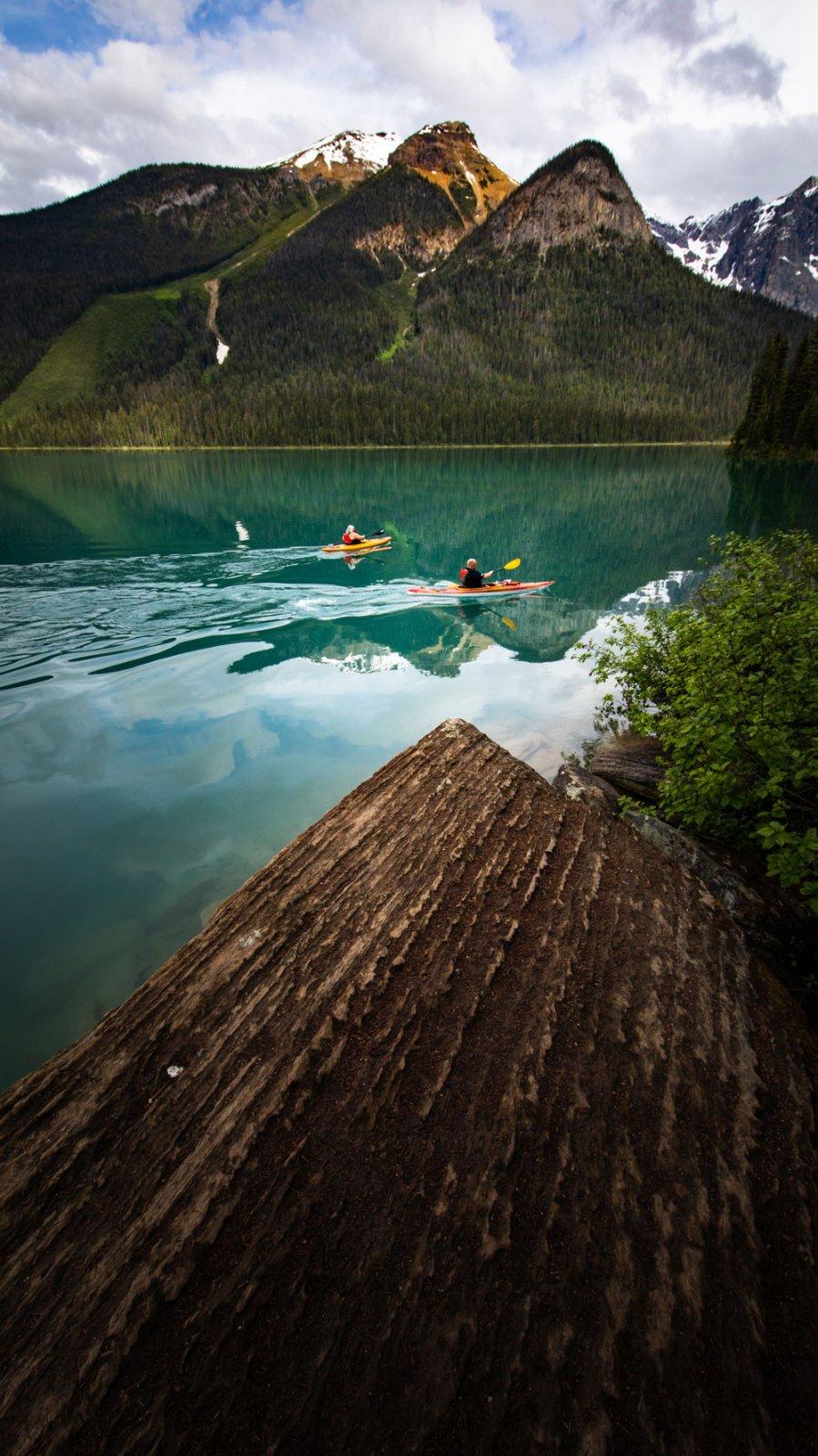 two kayakers paddling through calm water