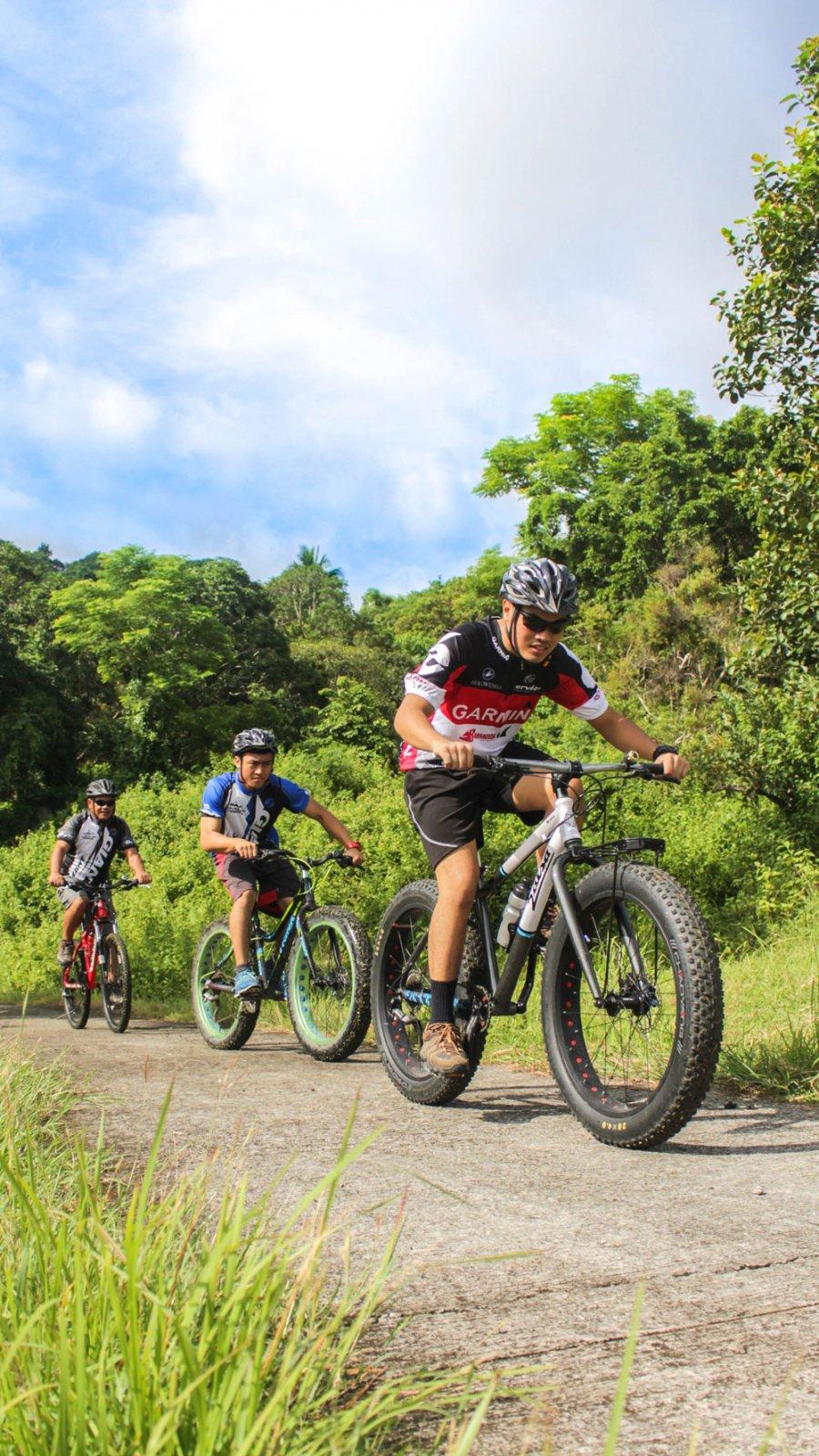 three mountain bikers moving uphill
