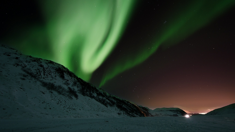 the green Northern Lights against a black sky