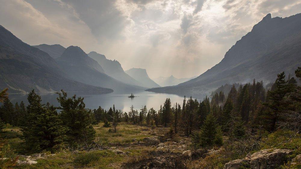 sun beams shining through the clouds over a mountain lake