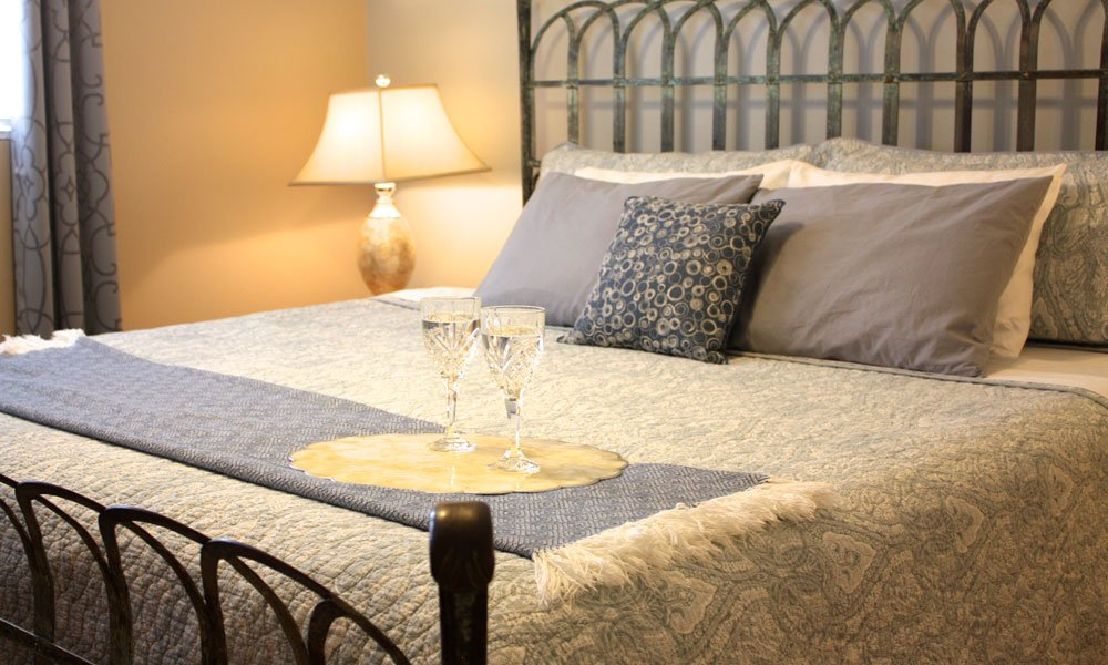 Iron bedframe and ornate spread with wineglasses
