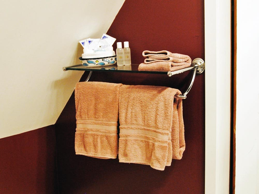 Towels on Rack Near Red Wall