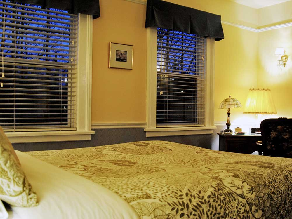 bed near a desk and two windows