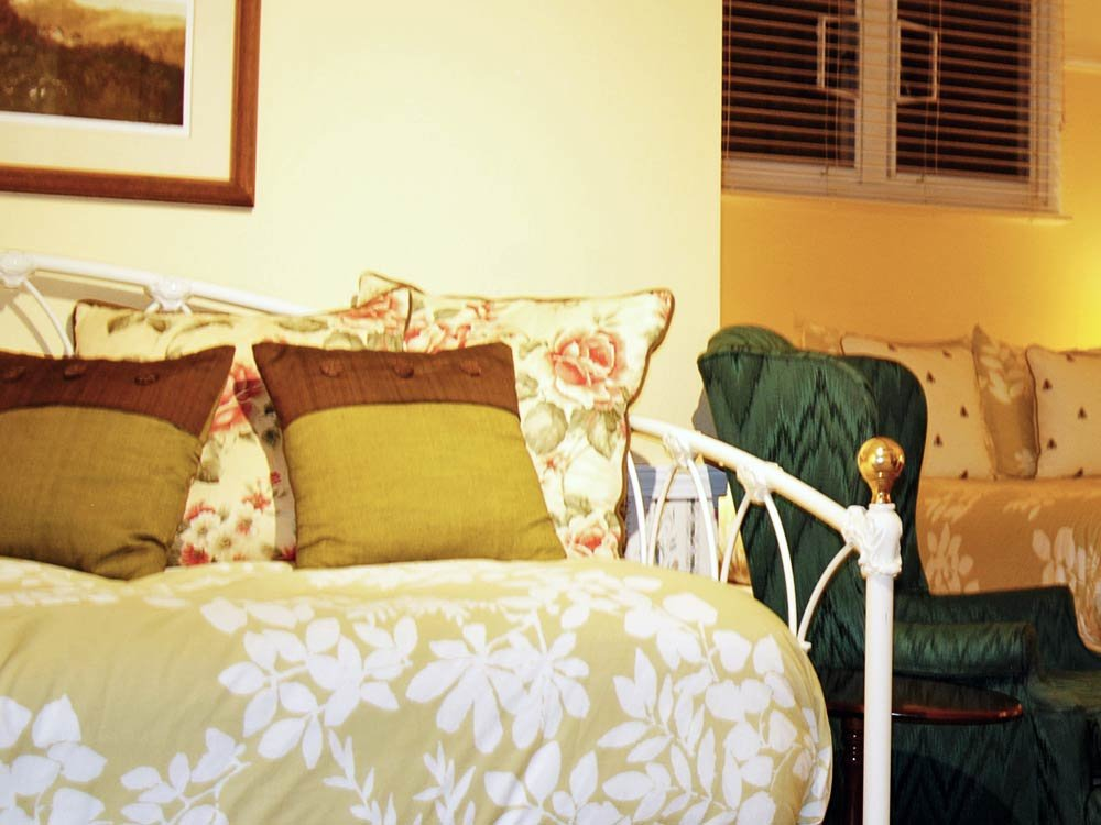 yellow bedding on white wrough iron daybed