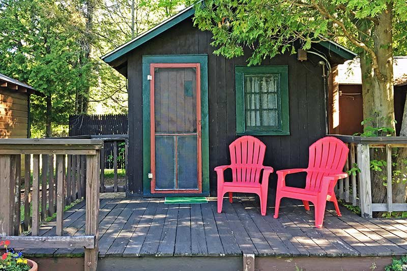 cabin with porch and two pink chairs