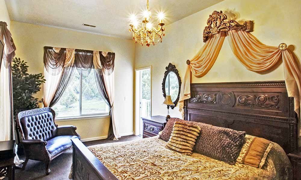 bed with ornate bedframe and chandelier