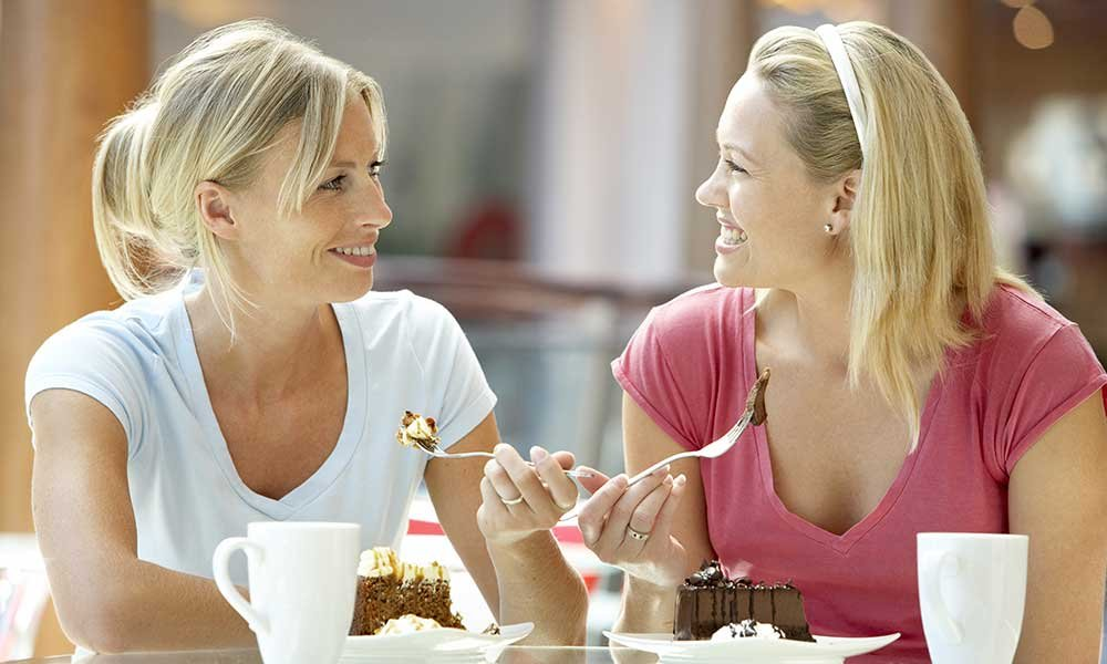 two women talking and eating
