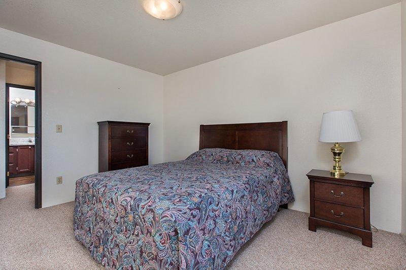 bedroom with door open to ajoining bathroom