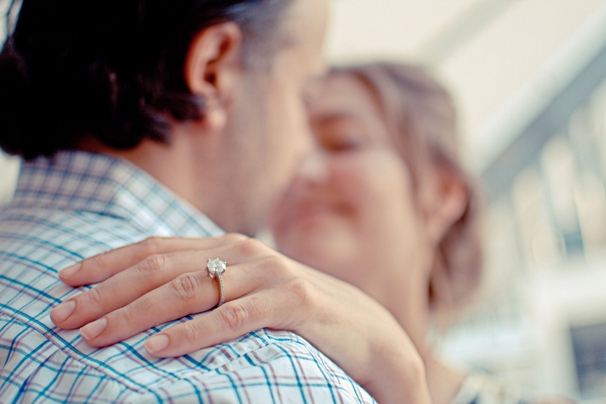 wedding ring on the hand of a couple embracing
