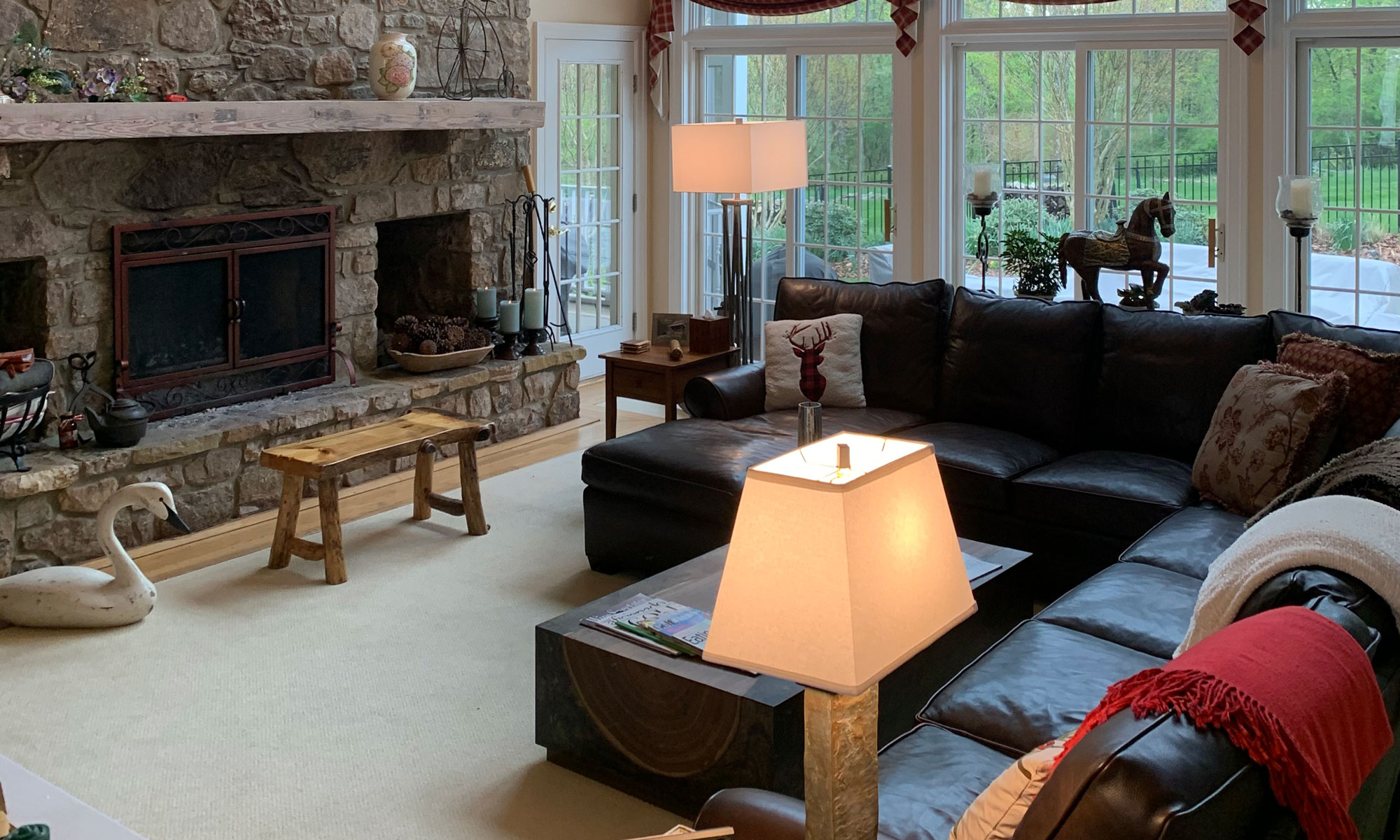 Couches across from fireplace in living room with large windows
