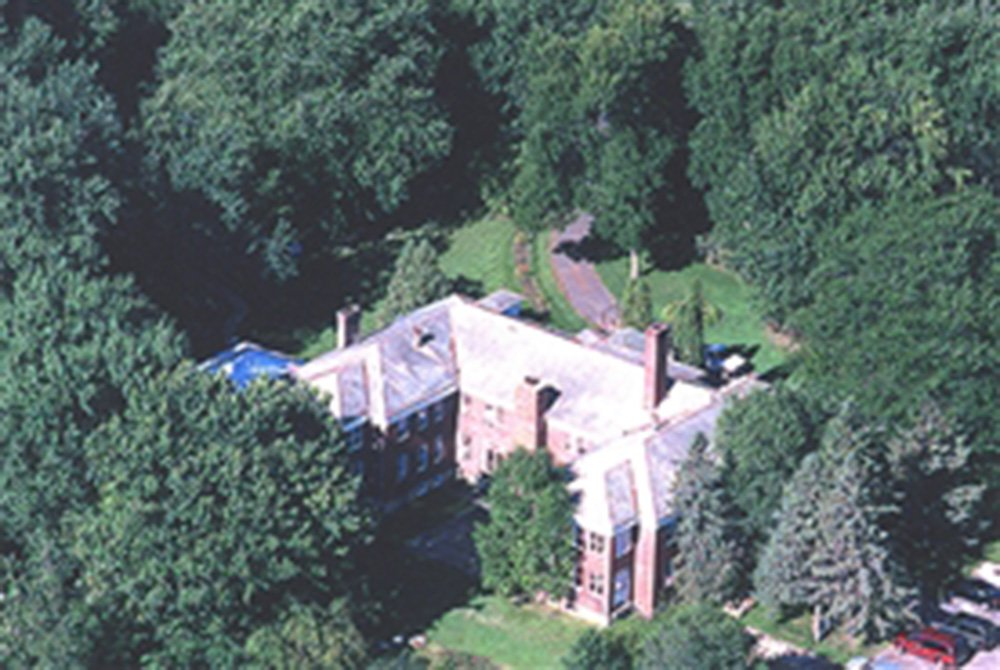 Birdseye view of large building in the middle of trees