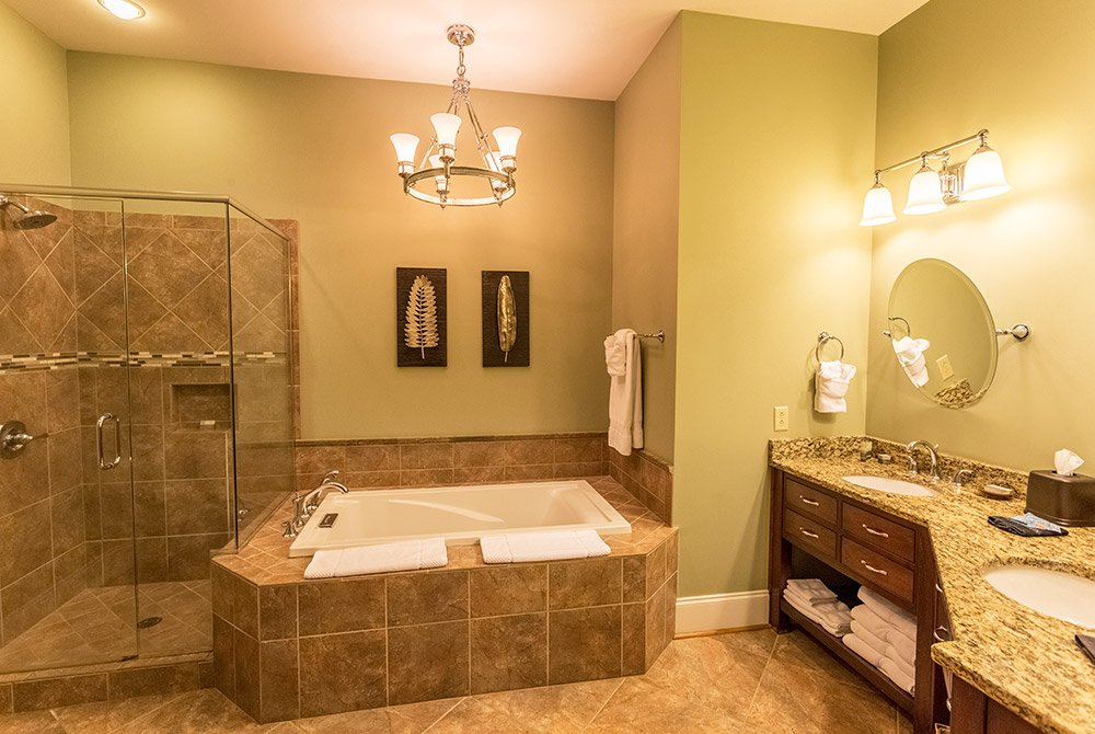 Glass shower, whirlpool tub, and double sinks in bathroom