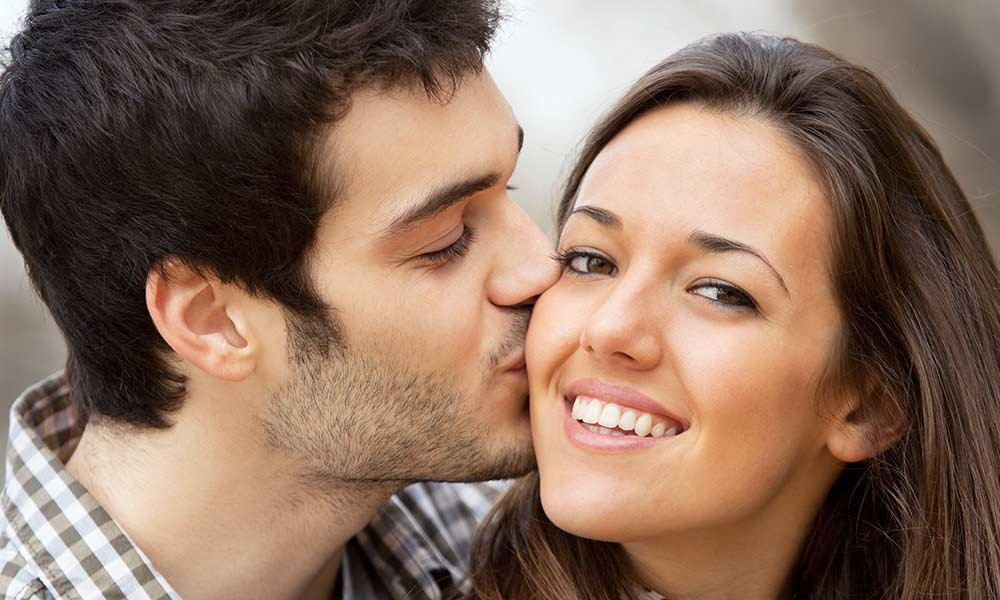 couple smiling and kissing the cheek