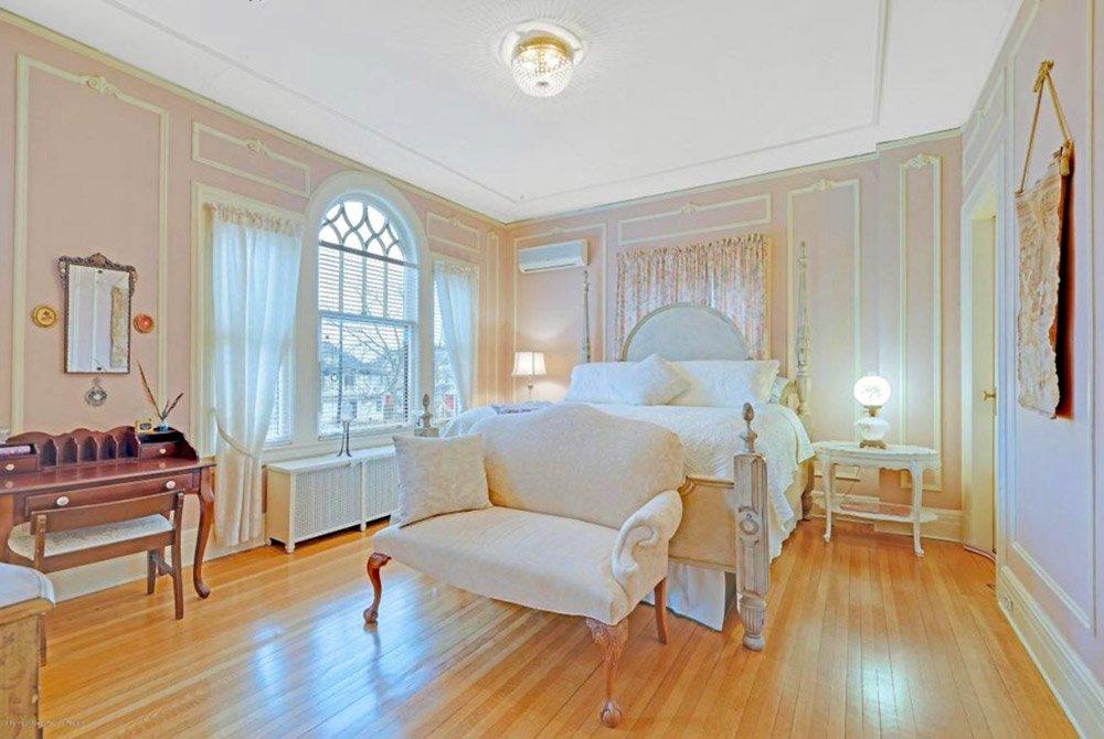 Window, desk, and loveseat around bed
