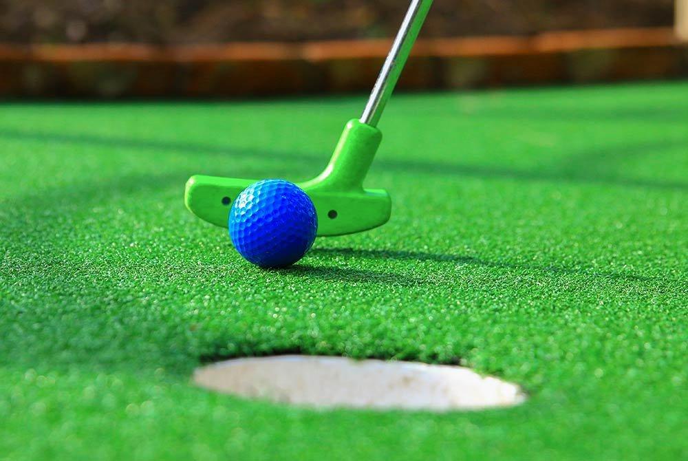 mini golf club hitting golf ball