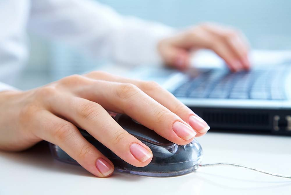 Woman using Mouse and Laptop