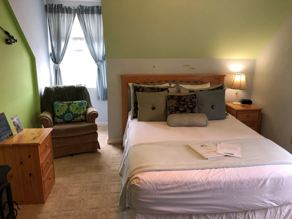 queen bed with lamp, pillows, and arm chair in front of window