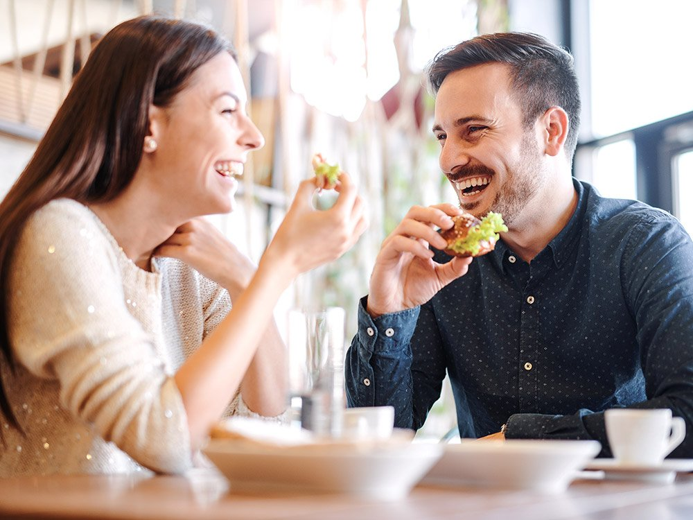 Man and woman laughing and eating food together