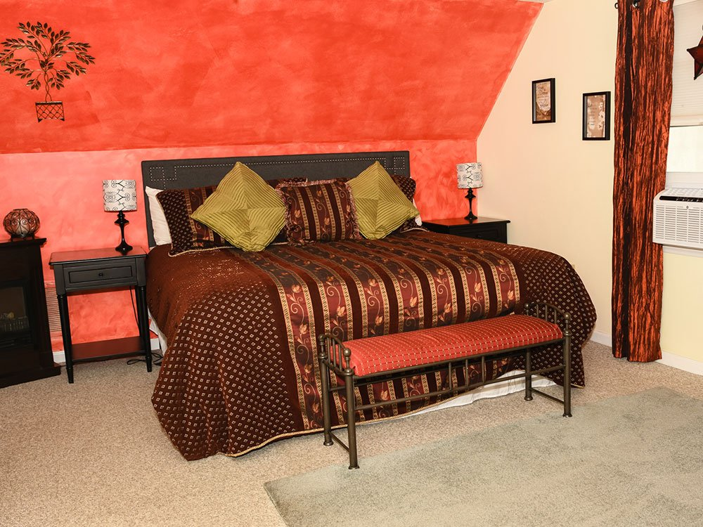 King-sized bed next to bedside tables and cushioned bench