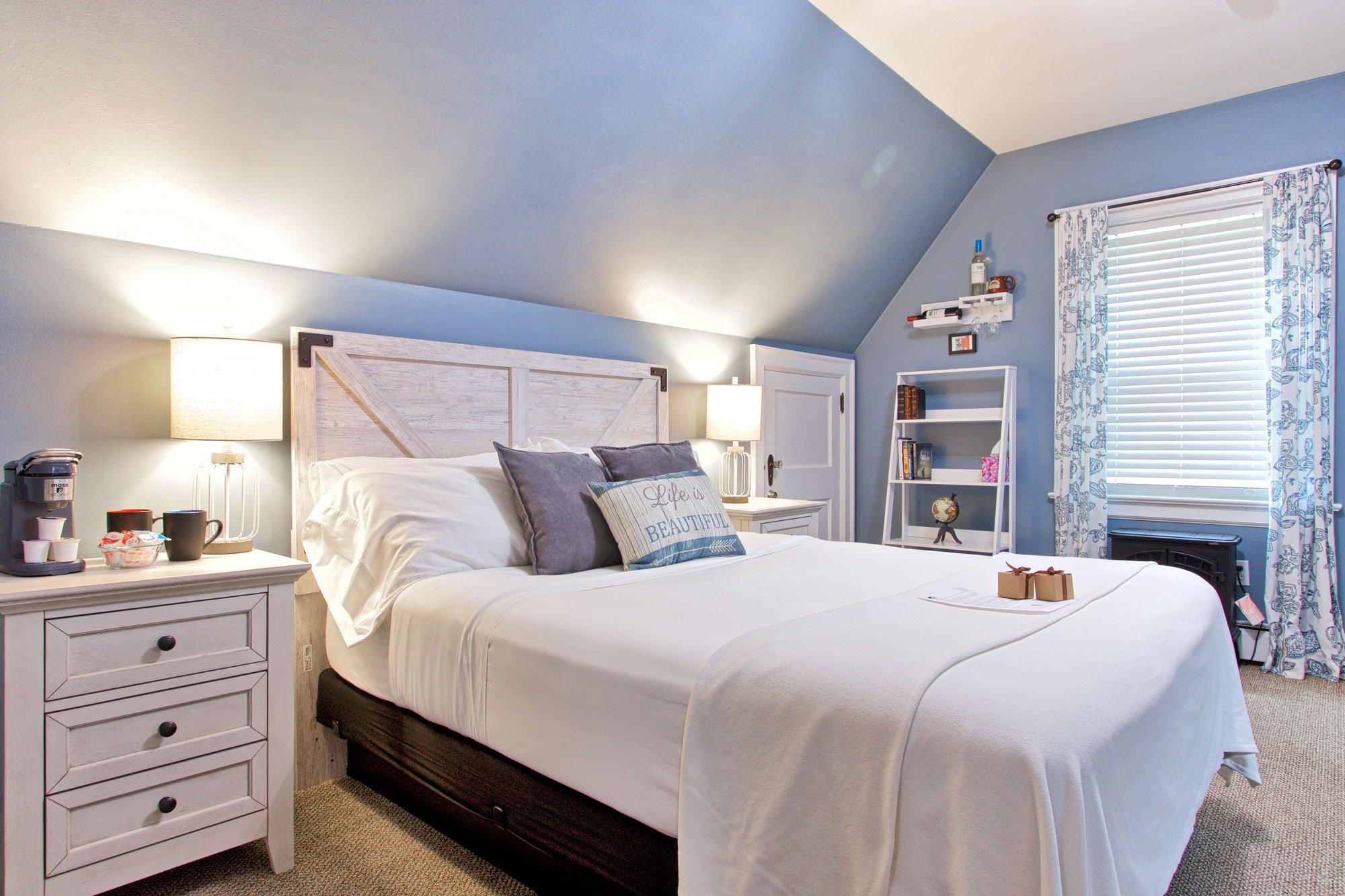 bed next to small door, window in background