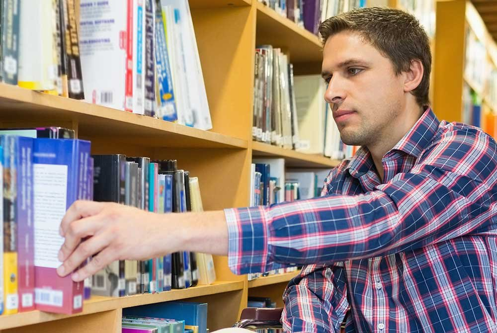 man selecting library book