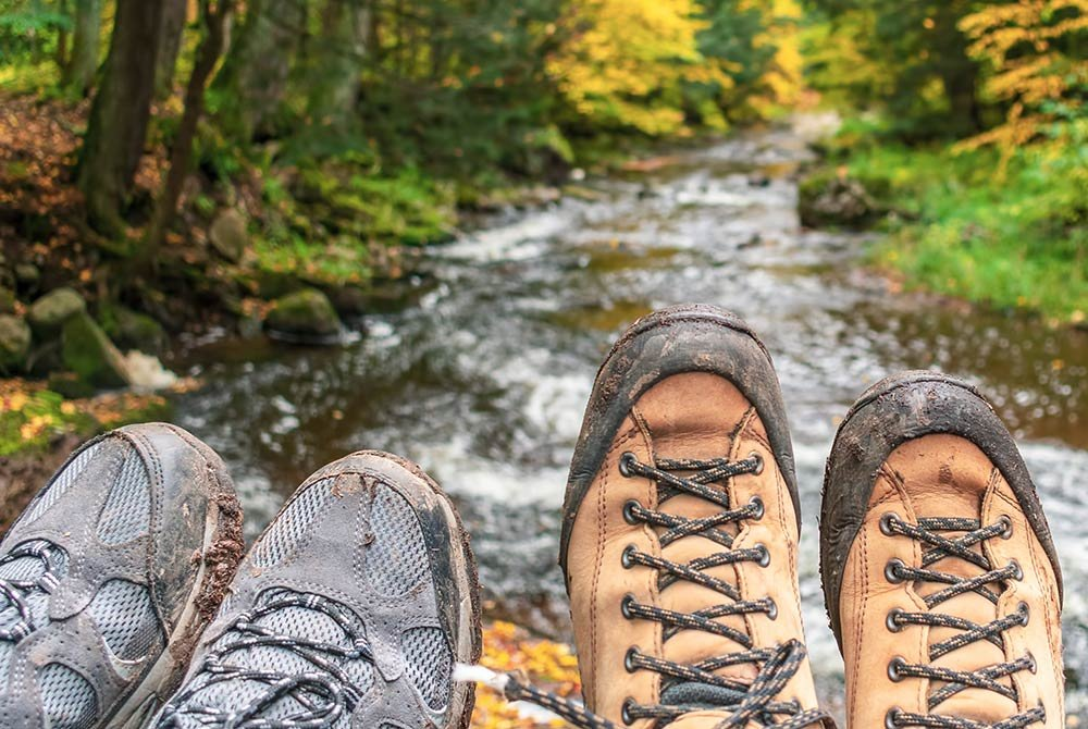 two pairs of hiking boots near river